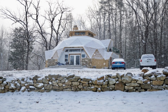 snow on a geodesic dome and rock wall