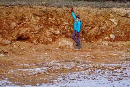 girl standing in excavated housepad in snow