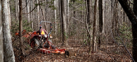 man on Kubota tractor with bush hog in woods