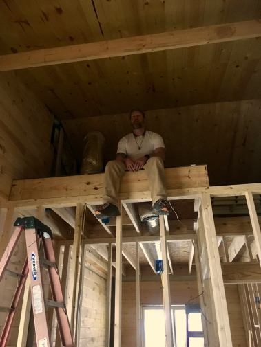 man sitting in loft being framed in with tongue and groove ceiling
