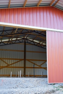red metal pole barn with gravel and rough plumbing