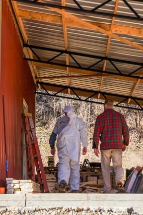 men walking into pole barn