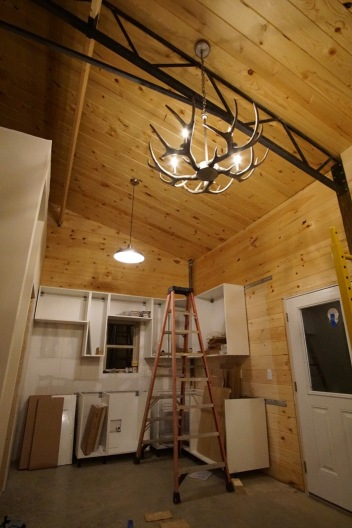 new construction IKEA kitchen installation in mountain cabin with antler chandelier