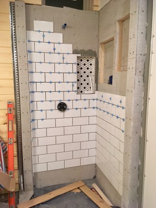 new construction shower being tiled