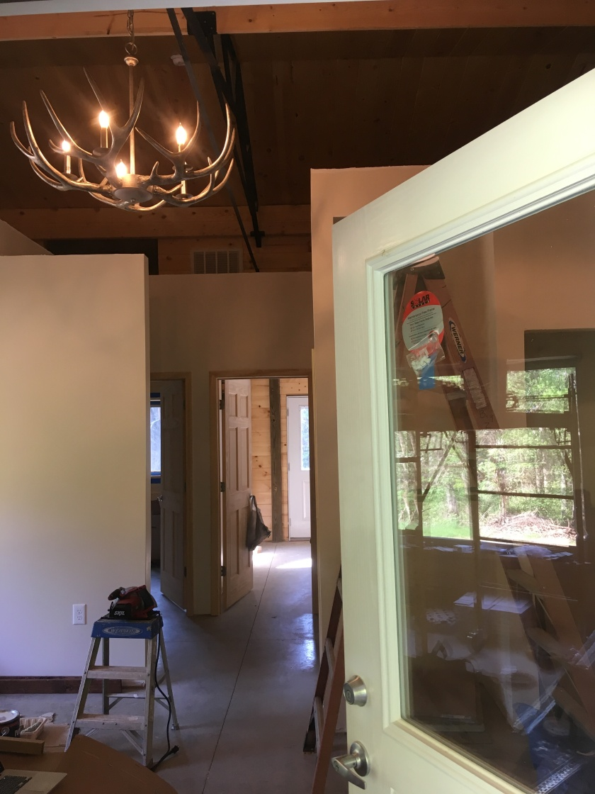 antler chandelier and open front door into house under construction