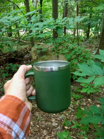 insulated coffee mug in the woods