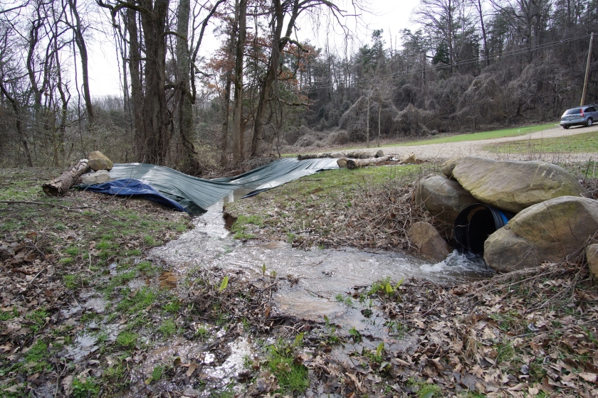 creek running from conduit into sinkhole under tarp