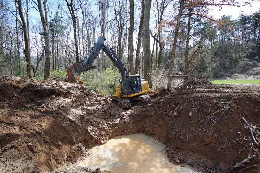 excavator by edge of sinkhole