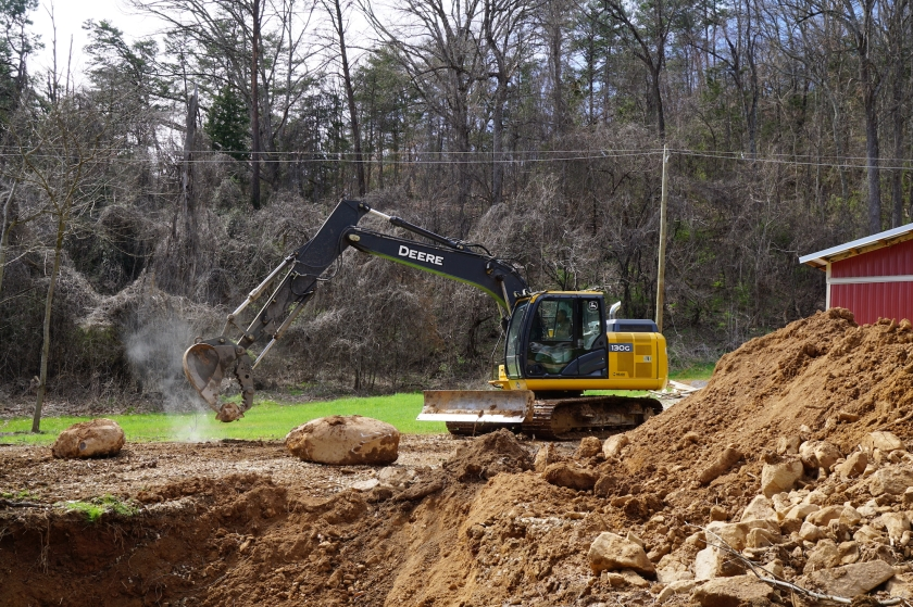 excavator moving rocks by edge of sinkhole