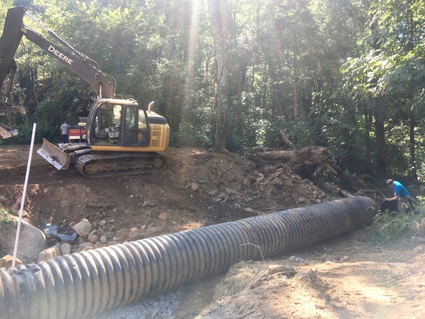 sinkhole being filled with excavator and conduit