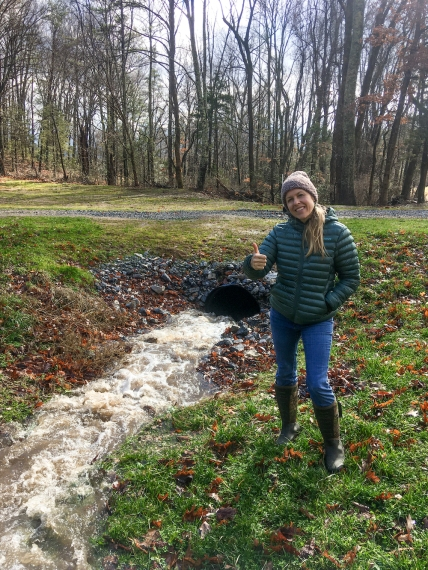 woman by creek running into a conduit