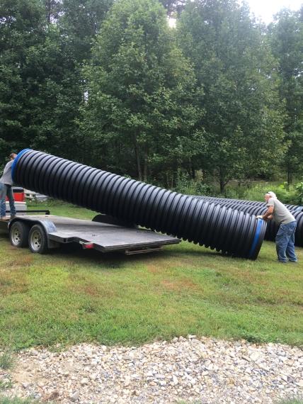 men unloading conduit from trailer